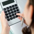 Woman's hands with a calculator and  pen — Stock Photo