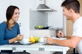Young Couple Enjoying Breakfast in the kitchen — Stock Photo