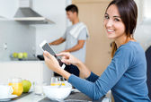 Couple in the kitchen preparing breakfast and browsing internet — Stock Photo