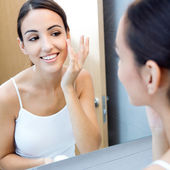 Portrait of young woman applying moisturizer cream on her pretty — Stock Photo