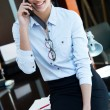 Cheerful businesswoman talking on phone standing in her office — Lizenzfreies Foto
