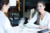 Two smiling business women have dinner at restaurant — Stock Photo