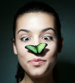 Surprised girl with a butterfly on her nose — Stok fotoğraf