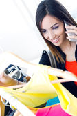 Young woman talking on the phone while shopping for clothes — Stock Photo
