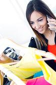 Młoda kobieta rozmawia przez telefon podczas zakupy na ubrania — Zdjęcie stockowe