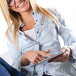 Beautiful young woman sitting at home with digital tablet — Stockfoto