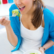 Pretty young woman eating salad at home — Stock Photo