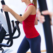 Happy young woman with elliptic machine in the gym — Stock Photo