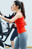 Young people with elliptic machine in the gym — Stock Photo