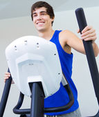 Happy young man with elliptic machine in the gym — Stock Photo