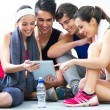 Young people looking at digital table in gym after making ex — Zdjęcie stockowe #38109723