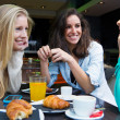 Three young friends having breakfast on a morning shopping in th — Stock Photo #39207707