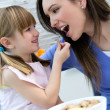 Child eating cereals with her mom in the kitchen — ストック写真