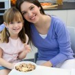 Child eating cereals with her mom in the kitchen — Stok fotoğraf