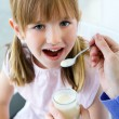 A young woman and little girl eating yogurt in the kitchen — Stock Photo #39495607