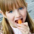 Cute little girl eats carrot and looking at the camera — Stock Photo