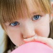 Cute little girl inflating a pink balloon in the kitchen — Stock Photo #39496125