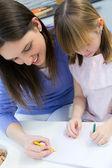 Criança desenhando com giz de cera com a mãe em casa — Fotografia Stock