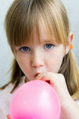 Cute little girl inflating a pink balloon in the kitchen — Stock Photo