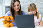Mother and daughter using laptop in the kitchen — Stock Photo