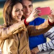 Young couple taking photos with smartphones in the park — Stock Photo