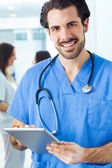 Cheerful young doctor looking at the camera — Stock Photo