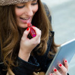 Young woman painting her lips with a digital tablet — Stock Photo