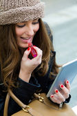 Young woman painting her lips with a digital tablet — Stockfoto