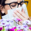 Stock Photo: Allergic to pollen young girl with bouquet of flowers