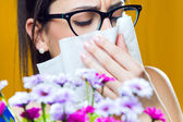 Allergic to pollen young girl with a bouquet of flowers — Stock Photo