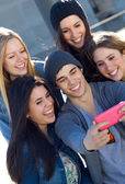 A group of friends taking photos with a smartphone — Stock fotografie