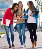 Students having fun with smartphones after class — Stock Photo