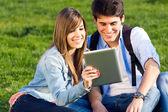 Young couple having fun with digital tablet — Stock Photo