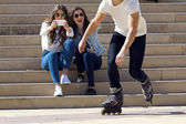 Roller skating boy with friends in town  — Stock Photo