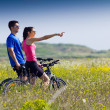Happy young couple on a bike ride in the countryside — Stock Photo #44448419