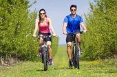 Joven pareja en un paseo en bicicleta en el campo — Foto de Stock