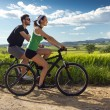 Happy young  couple on a bike ride in the countryside — Stock Photo #45964495