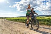 快乐在乡下骑一辆自行车上的年轻夫妇 — 图库照片