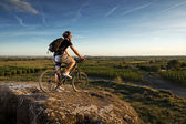 Young man riding mountain bike — Stock Photo