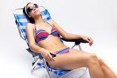 Vacker ung kvinna med bikini som sitter på en strandstol — Stockfoto