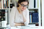 Jovem mulher trabalhadora, lendo o jornal no escritório — Fotografia Stock
