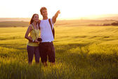 Happy Young couple on the field in spring — Stock Photo