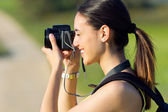 Happy Young girl taking photos in the field — Stock Photo