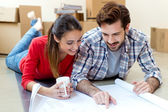 Young couple looking at the blueprints of their new home — Stock Photo