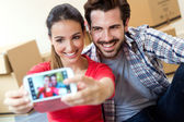Young couple  taking selfies in their new home — Stock Photo