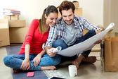 Mladý pár při pohledu na plány jejich nového domova — Stock fotografie