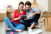 Young couple with digital tablet in their new home — Stockfoto