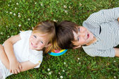 Happy young brothers lying on grass  — Stock Photo