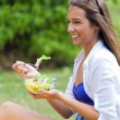 Beautiful young woman holding green salad, outdoors — Stock Photo #48156425
