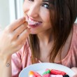 Cute young woman eating jelly candies with a fresh smile — Stock Photo #48214441